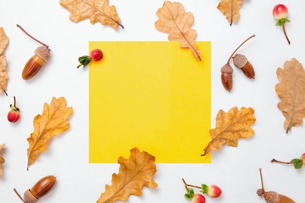 白い背景にオークの葉とどんぐりのパターン。テキストの黄色の空白フレーム。秋のモックアップ。最小限の秋の構成、秋のコンセプト。フラットレイ、トップビュー、コピースペース。