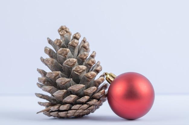 Un cono di quercia con palline rosse scintillanti su fondo bianco