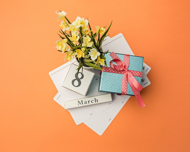 Oange desk with gift, flowers and notebook