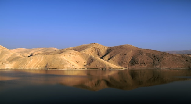 Oasis in the middle of desert - reflection of desert mountains on the lake surface