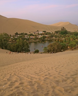 The oasis town of huacachina as seen from the sand dune at sunset, ica region, peru