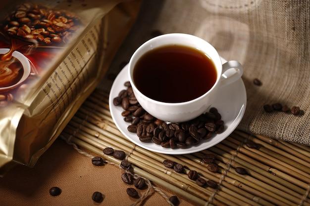 Обжаренные кофейные зерна и чашка кофе на деревянном столе