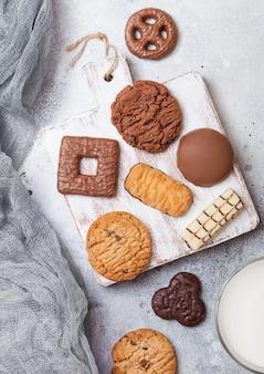 石造りのキッチンで木の板に牛乳のガラスとオート麦とチョコレートクッキーの選択