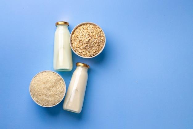 Овсяное и рисовое веганское молоко в стеклянных бутылках на синем