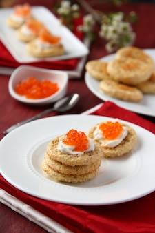 Oat bran cookies with red caviar and cream cheese