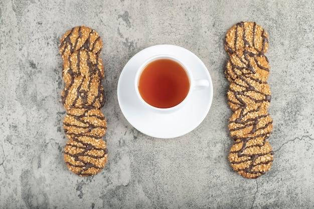 Овсяное шоколадное печенье с чашкой черного чая на камне.