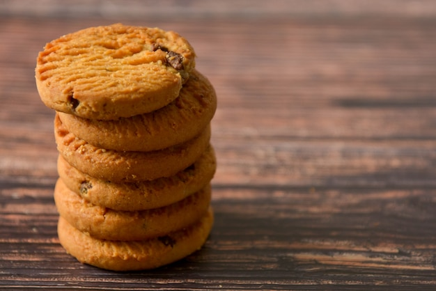 Oat and chocolate chip cookies on rustic wooden table background, copy space.