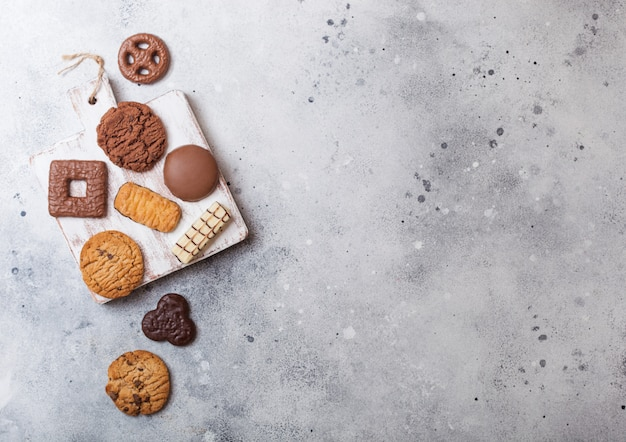 Oat and chocolate cookies selection on wooden board on stone kitchen