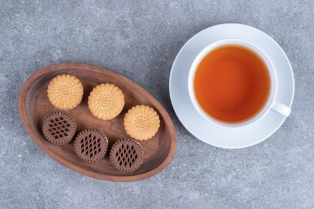 Biscotti di avena e cacao con tazza di tè su superficie di marmo