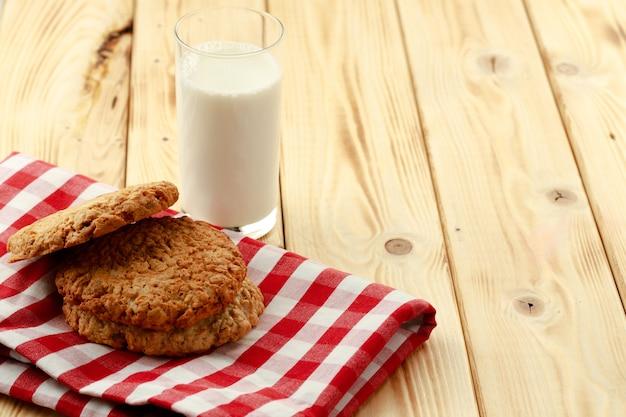 Овсяное печенье и стакан молока на деревянном столе
