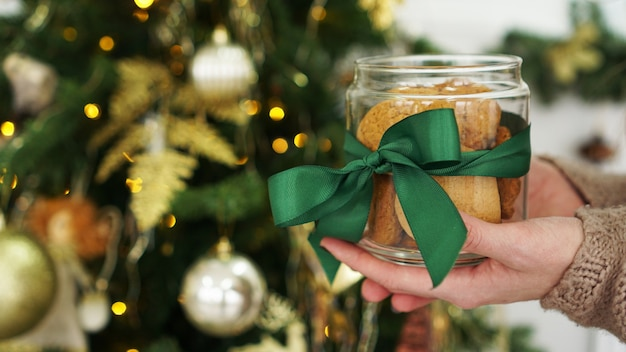 Oat cookies in a glass jar. against the background of christmas decor