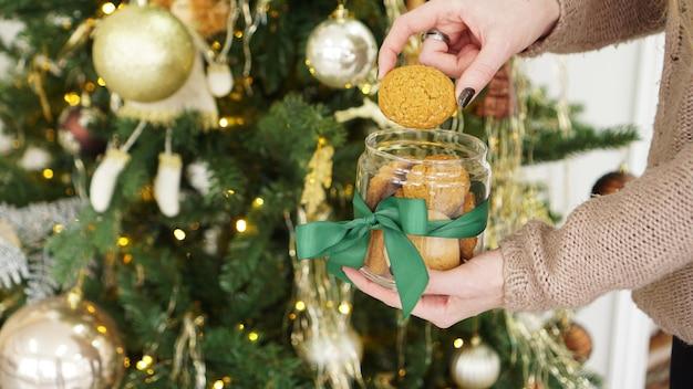ガラスの瓶に入ったオート麦クッキー。クリスマスの装飾を背景に
