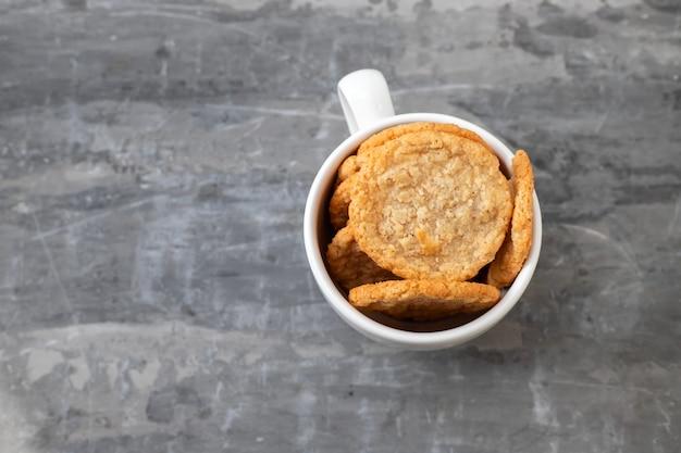 セラミックの背景に白いカップのオートクッキー