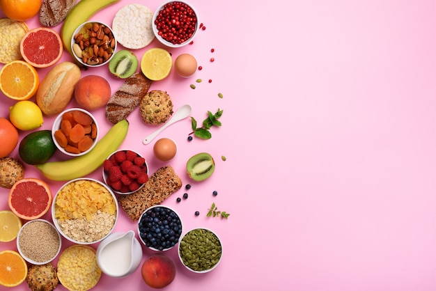 Oat and corn flakes, eggs, nuts, fruits, berries, toast, milk, yogurt, orange, banana, peach on pink background.