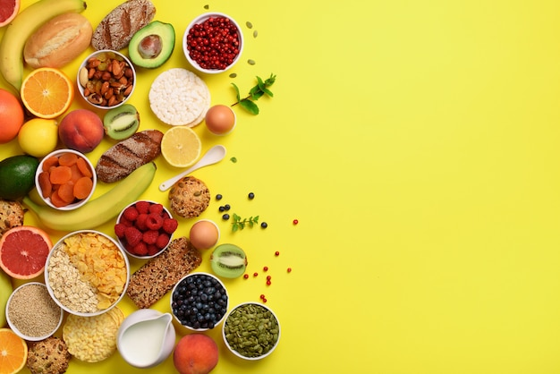 Oat and corn flakes, eggs, nuts, fruits, berries, toast, milk, yogurt, orange, banana, peach on yellow background.