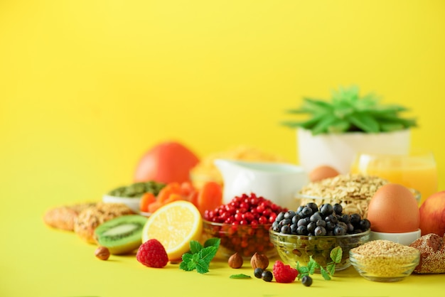 Oat and corn flakes, eggs, nuts, fruits, berries, toast, milk, yogurt, orange, banana, peach