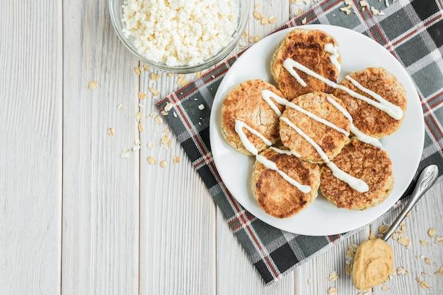 흰색 나무 바탕에 사 우 어 크림과 땅콩 버터와 함께 귀리 코 티 지 치즈 팬케이크.