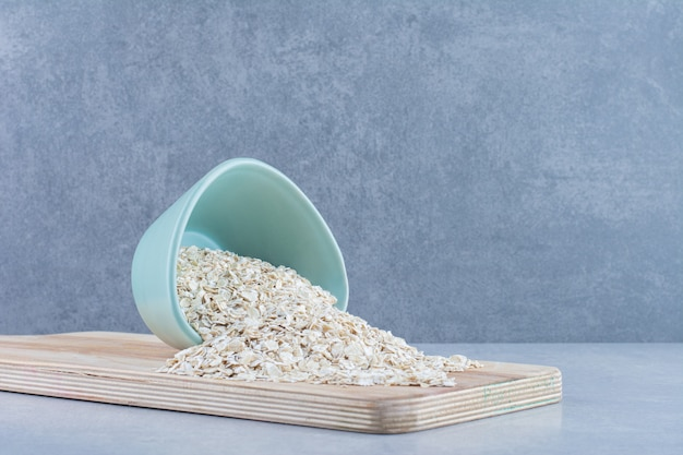 Oat flaked poured on a wooden board from a small bowl on marble background.