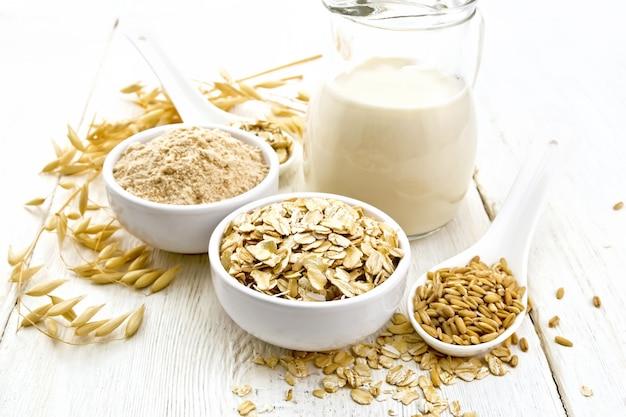 ボウルにオーツ麦フレークと小麦粉、スプーンに穀物、ガラスの水差しにオートミールミルク、軽い木の板にオーテンの茎を当てる