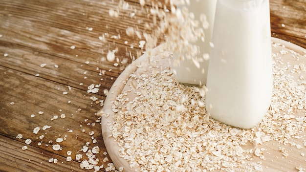 Oat flakes and bottle of fresh milk on a wooden board. wooden rustic background