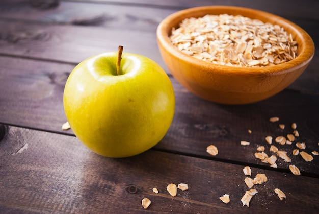 Oat flakes in bowl and one apple