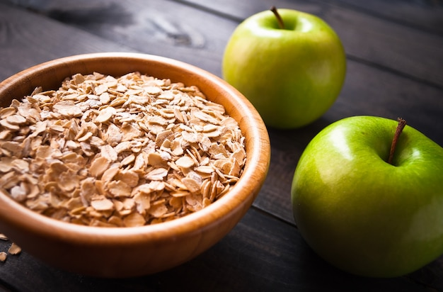 Oat flakes in bowl and two apples
