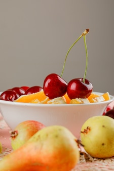 Oat flakes in a bowl with pear, orange and cherries