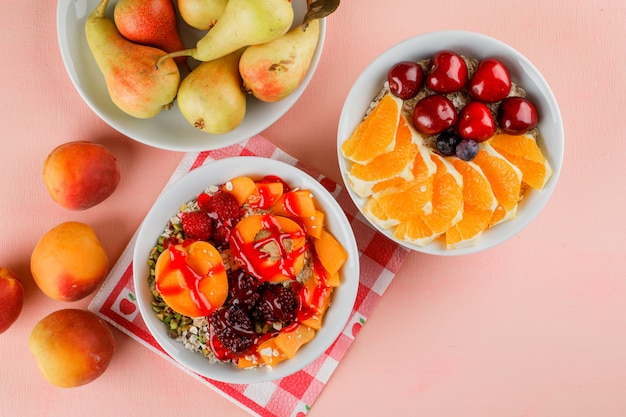 Oat flakes in bowls with nuts, apricot, berries, pear, cherry, orange