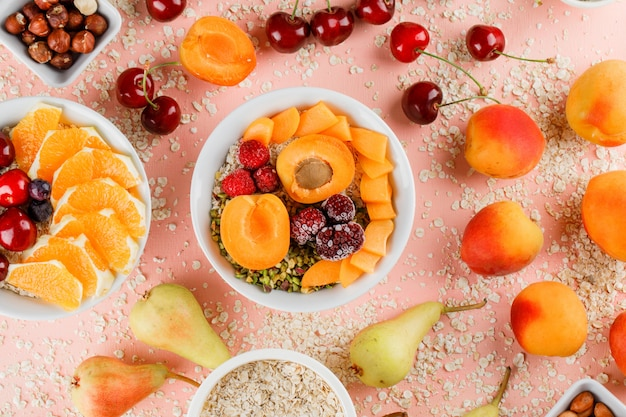 Oat flakes in bowls with pear, orange, cherry, apricot, nuts