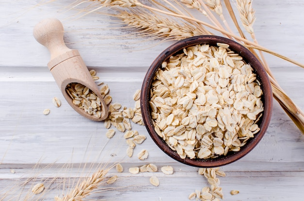 Oat flakes  in ceramic bowl and wooden spoon and spikelets