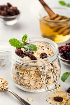 Oat flakes in glass jar with honey, raisins and nuts. healthy breakfast concept.