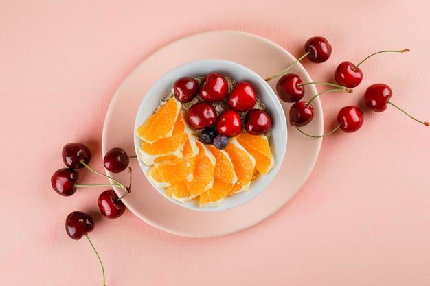 Овсяные хлопья в миске с вишней, апельсином, ягодами