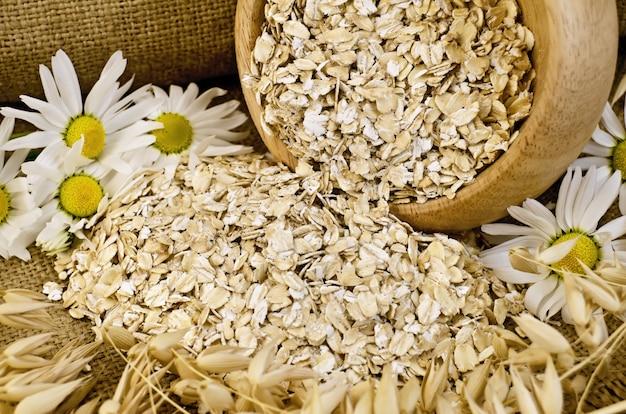 木製のボウルにオーツ麦のフレーク、オーツ麦の茎、荒布と木の板にカモミール