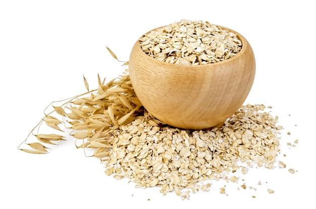 木製のボウルにオーツ麦フレーク、オーツ麦の茎、白い背景で隔離のテーブルに散らばっているオーツ麦フレーク