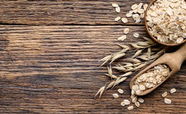 古い素朴な板の木製の背景に木製のスクープとオーツ麦の植物とボウルのオーツ麦フレーク。上面コピースペース