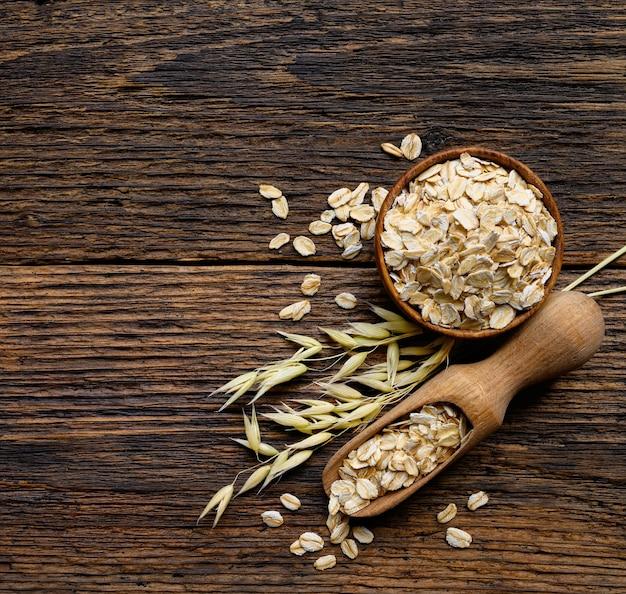 古い素朴な板の木製の背景にスプーンとオーツ麦植物と木製のボウルにオーツ麦フレーク。上面コピースペース