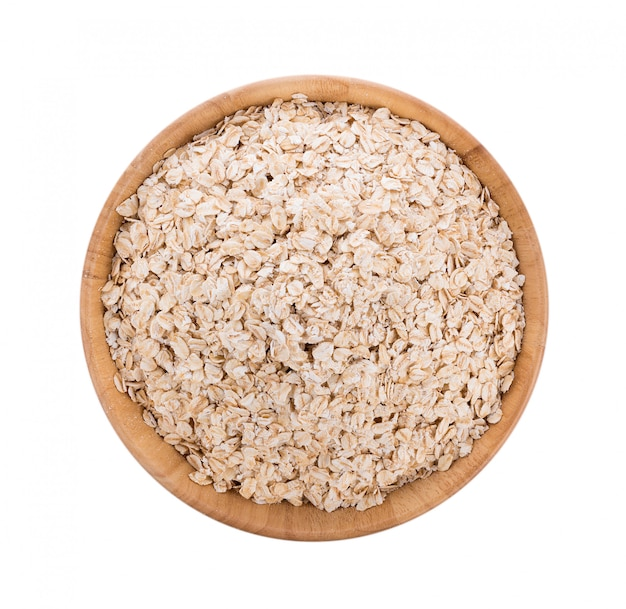Oat flakes pile in bowl on white