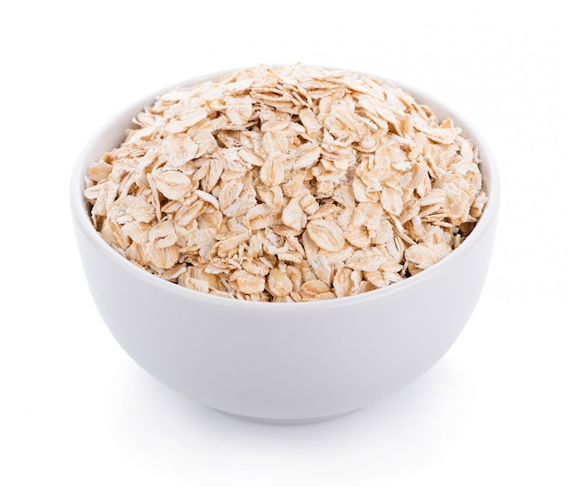 Oat flakes pile in white bowl on white wall