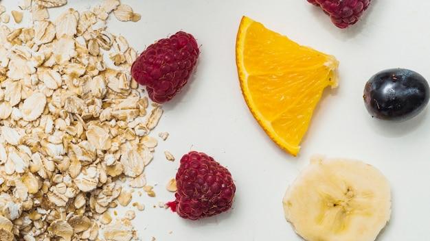 Oat flakes; raspberry; grapes; slice of lemon and banana on white background