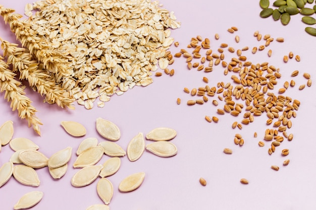 オーツ麦のフレーク、小穂、小麦の粒。かぼちゃの種。フラットレイ。ピンクの背景