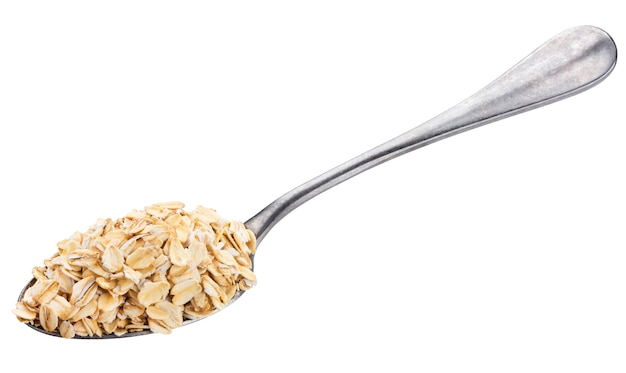 Oat flakes in spoon isolated on white