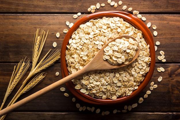 그릇에 귀리 플레이크 요리하지 않은 귀리 건강한 식생활 채식주의 음식 건강 식품 아침 식사의 개념