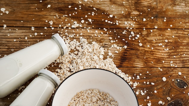 Oat flakes in white bowl and bottles of fresh milk. wooden rustic background