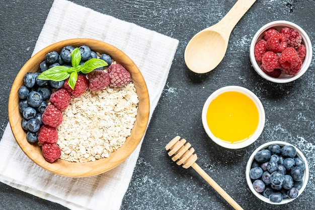 Oat flakes with berries and honey in the wooden bowl top view. healthy breakfast idea.