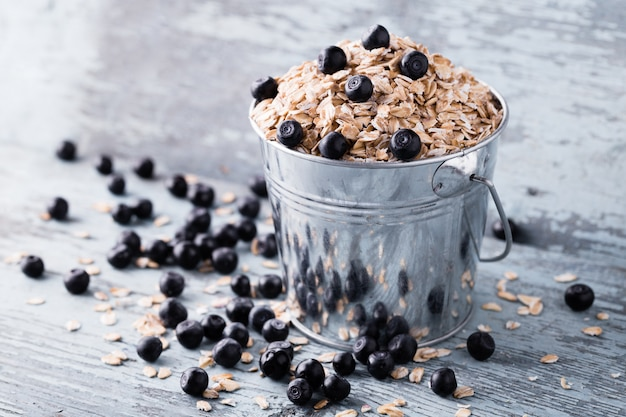 Oat flakes with blueberry in a bucket on wood.