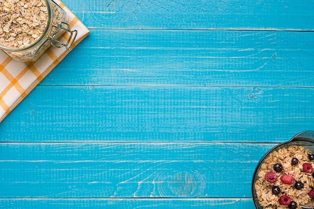 우유와 딸기가 든 귀리 플레이크는 푸른 나무 배경에 숟가락이 달린 그릇입니다. 아침 식사를 위한 건강식. 평면도. 복사 공간