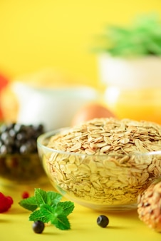 Oat flakes with milk, fresh berries, yogurt, boiled egg, nuts, fruits, orange, banana, peach for breakfast on yellow background