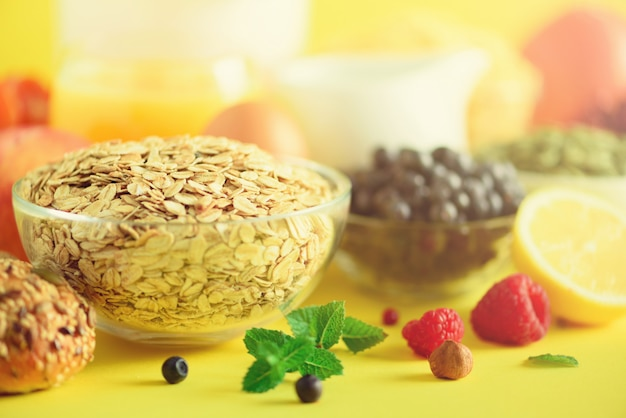 Oat flakes with milk, fresh berries, yogurt, boiled egg, nuts, fruits, orange, banana, peach for breakfast on yellow background.