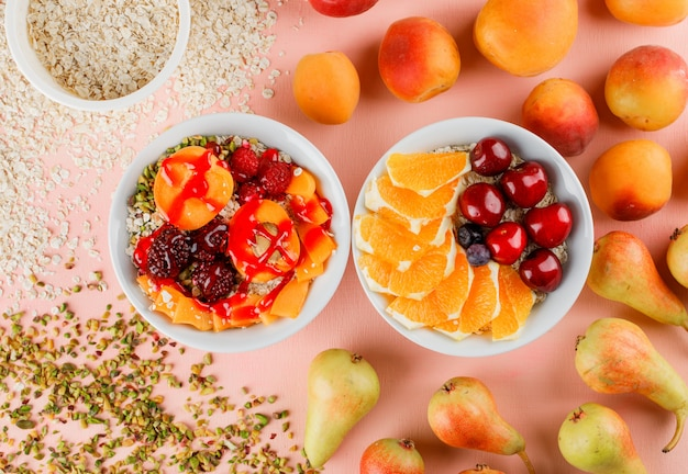 Oat flakes with nuts, cherry, orange, berries, pear, apricot in bowls