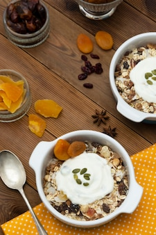 Oat flakes with nuts, dried fruit mix in bowl over rustic wooden table